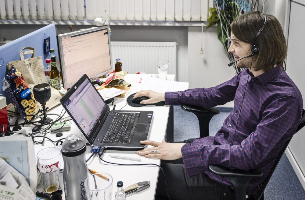 mężczyzna siedzi przy biurku komputerowym