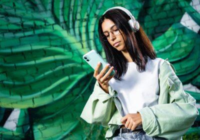 używa smartfona na zielonym tle